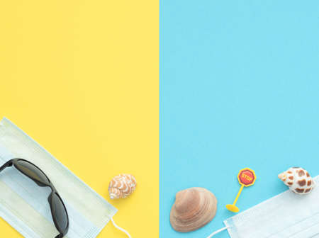 Sunglasses, shells and stop road sign lie on medical face masks on double blue and yellow background. Travel at home, quarantined holiday, canceled summer vacation, travel during coronavirus concept.