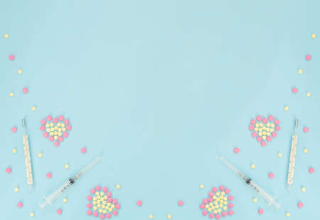 Hearts made of pink and yellow pills, thermometer, syringe on light blue background. Seasonal diseases. Medicine concept. Flat lay style with copy space, top view.