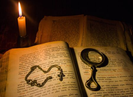 The nude cross and the old magnifying glass lie on ancient prayer books written by the Cyrillic under the light of a wax candle Stock Photo