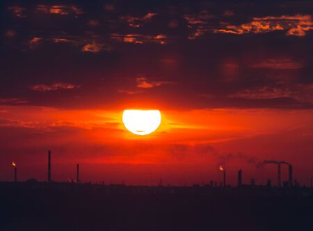 Rising sun over factory pipe silhouettes