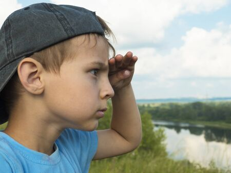 Little boy with untidy bangs in a baseball cap looks out over the horizon