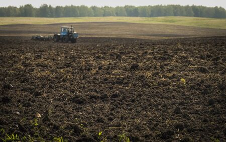 TraPlowed plowland with black earth in an autumn field with defocused tractors equipped with a disc plow in the backgroundctors plow plowland on an autumn clear day