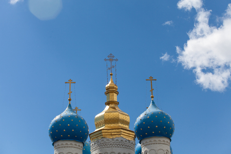 Golden domes of the Russian Church against a blue sky with clouds