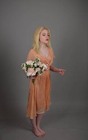 Girl in lilac dress posing in photo studio