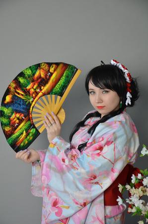 A girl in a yukata next to cherry twigs
