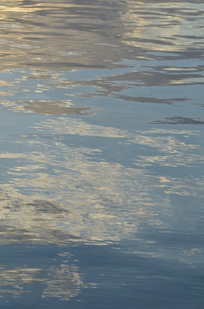 reflection of blue sky with white clouds in water, abstract background.
