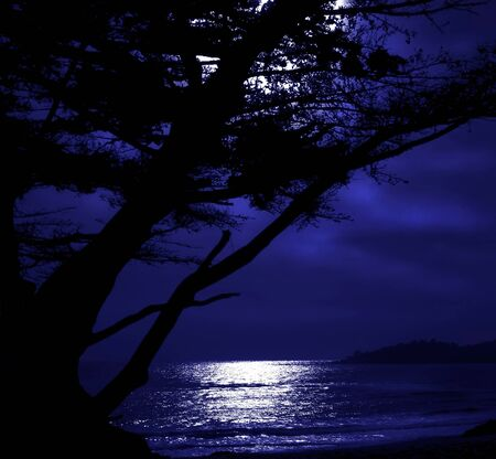 tranquil atmosphere: Beautiful Blue filtered version of a Carmel Moonrise Stock Photo