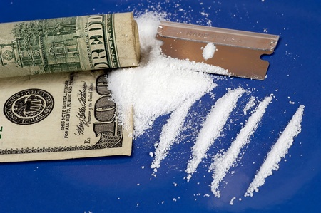 One hundred dollar bill with chopped cocaine and razor blade Stock Photo