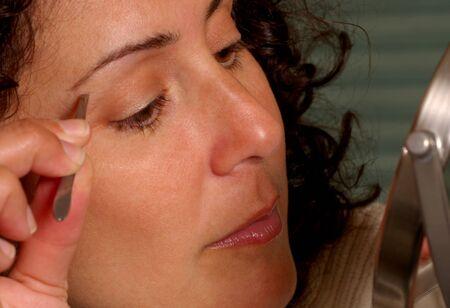 tweezing: Woman Tweezing Eyebrows