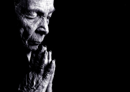 Portrait on Black Of Old woman Praying Stock Photo
