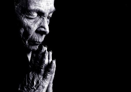 vieux: Portrait sur noir de vieille femme Prier