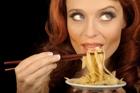 supper: Nice Image of a Woman eating Pasta with chopsticks Stock Photo