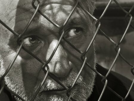 A Striking Image of a Latino man behind a cage photo