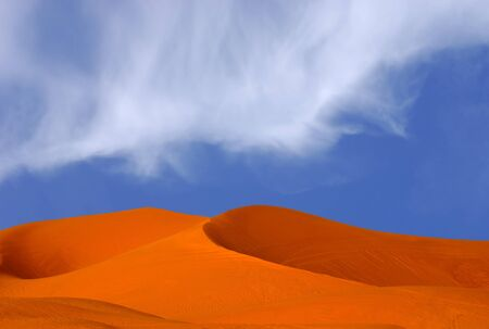 beautiful Image Of Red Sand Dunes with Blue sky and clouds photo