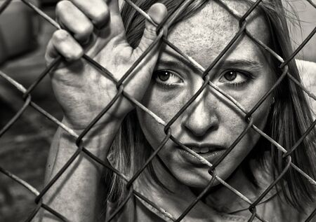 Nice Image of a woman behind a chain Link Fence