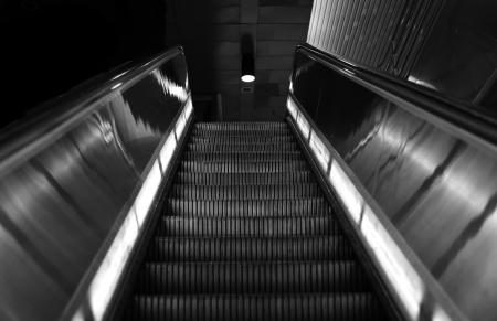 bajando escaleras: Bonita imagen dramática de una escalera mecánica moderna en Blanco y Negro Foto de archivo