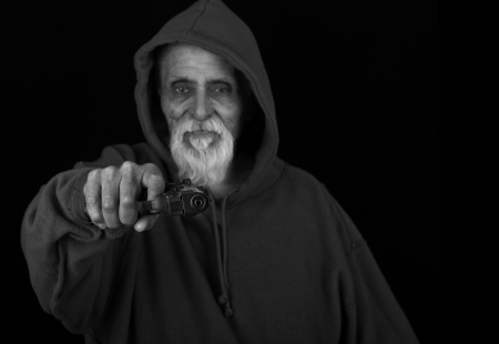 tough man: Very scary Image of a senior Latino with a Pistol pointed at the camera Stock Photo