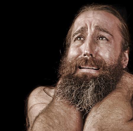 Imagen muy emocional de un hombre con barba sin hogar llanto