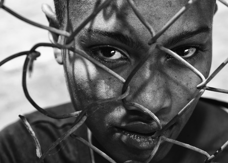 anti racist: Beautiful Image of a afro American woman behind a fence, depicting Racism Stock Photo
