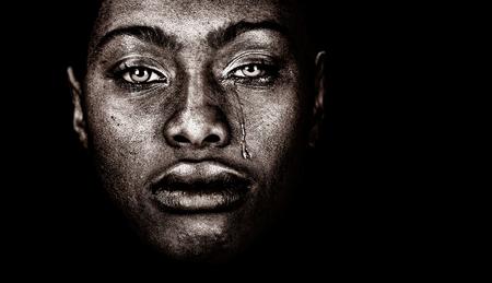 Zeer sterk beeld van een Afro-Amerikaanse vrouw huilen geïsoleerd op zwart Stockfoto