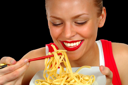 plateful: Woman eating Pasta on Black with chopsticks