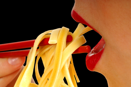 plateful: Woman With Pasta and chopsticks Stock Photo