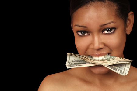 stealing money: Money In Her Mouth with a Black Background Stock Photo
