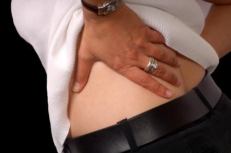 salud y deporte: Manos de una mujer con dolor de espalda Foto de archivo