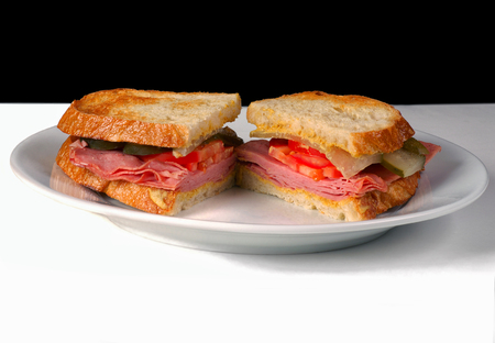 smoked: Sliced Ham Sandwich on a white Plate with Black Background
