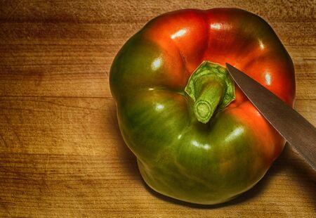 A Beautiful Unique Multi colored Pepper On a cutting Board