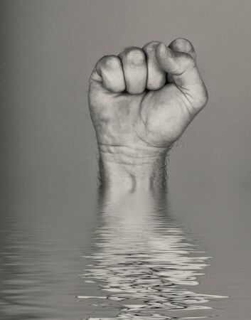 Mans Fist comes out of the water with reflection
