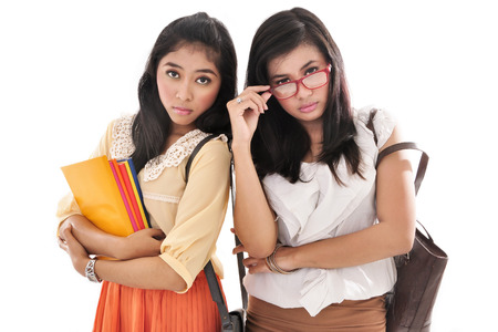 sixteen: two beautiful women carrying books and bags, isolated on white background
