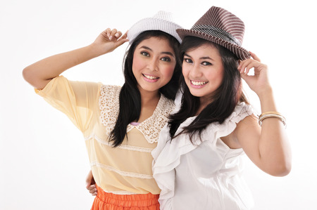 sixteen: two beautiful girl wearing a hat, isolated on white background