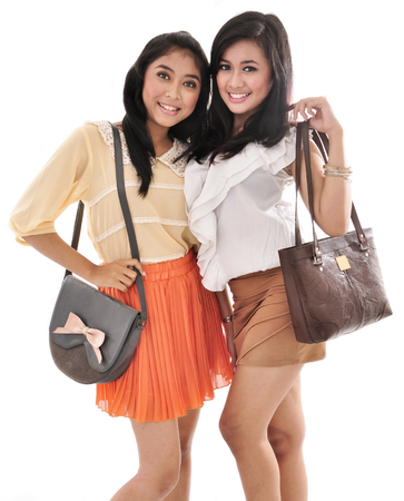 sixteen: two sexy girls carrying bags, isolated on white background