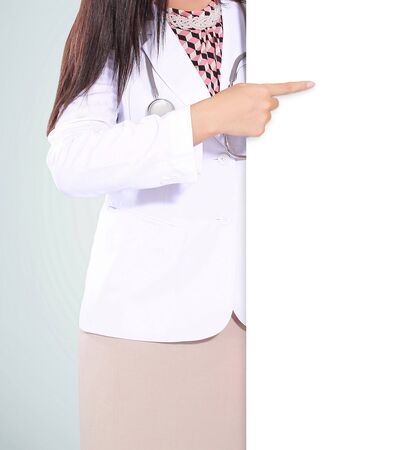 doctor holding gift: beautiful woman doctor smiling and pointing a blank board, isolated on green background