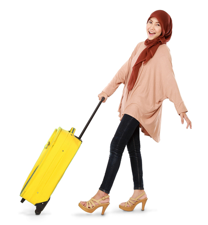 cheerful young muslim woman carrying a suitcase isolated on white background