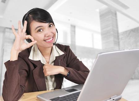 jovenes empresarios: Jóvenes empresarios forman las manos bien y trabajan con el portátil y el uso de un auricular, en la oficina