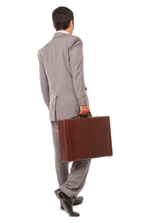 office shoes: back view of a business man standing and holding a briefcase, isolated on white background