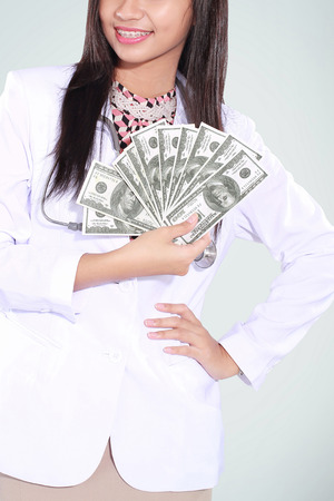 doctor with dollars: female doctor carrying a lot of money dollars, isolated on green background