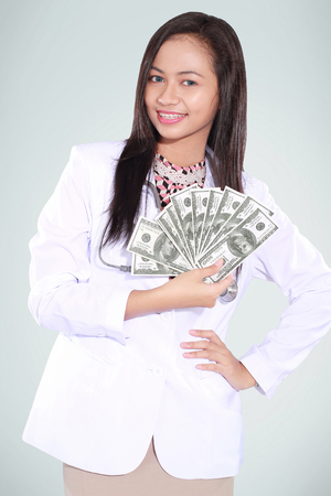 doctor money: female doctor carrying a lot of money dollars, isolated on green background