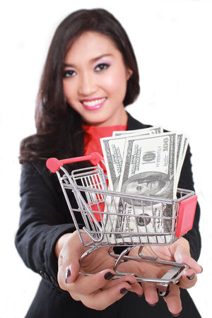 saleslady: young businesswoman carrying a shopping cart containing a lot of money dollars, isolated on white background