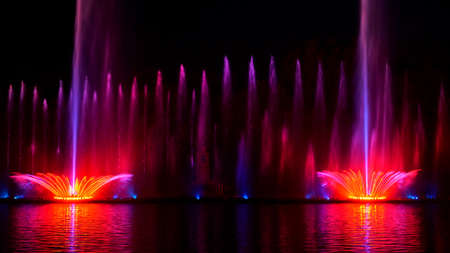 Night laser fountain show, on the Roshen embankment, the Ukrainian city of Vinnitsa.Musical fountain with laser animations.Musical fountain Roshen in Vinnitsa, Ukraine.Evening show Roshen fountain. Standard-Bild