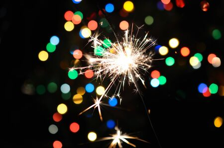 Christmas sparkler and background of colorful bokeh photo