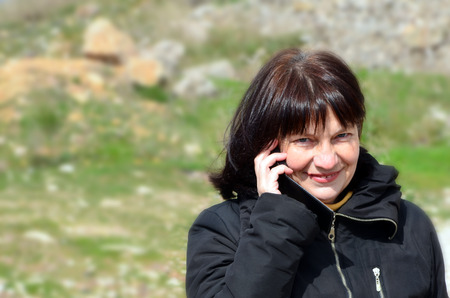 Portrait of pretty woman with mobile phone outdoors