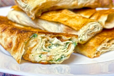 Lavash with sour cream and greens on the plate