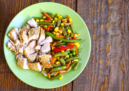 Tasty fried bean with vegetables and chicken on plate at wooden desk, top view