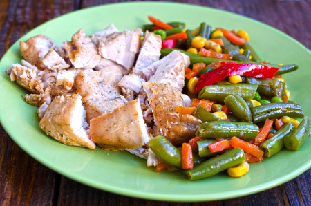 Tasty fried bean with vegetables and chicken on plate at wooden desk