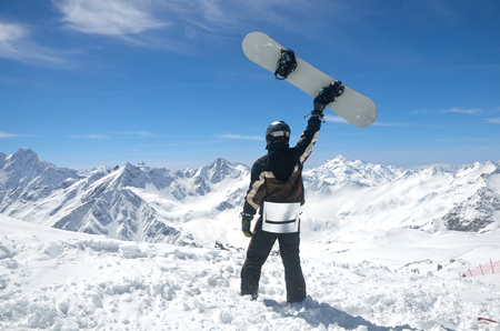 Man with snowboard standing at the Caucasus MountainsElbrus Stock Photo