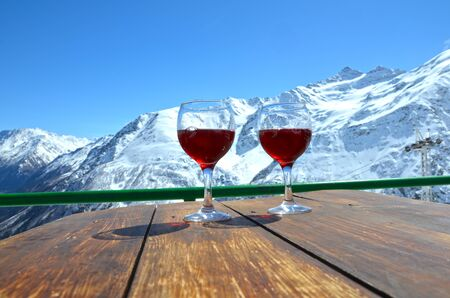 Close up of glass with red wine over landscape of caucasus mouintains in sunny day, Elbrus