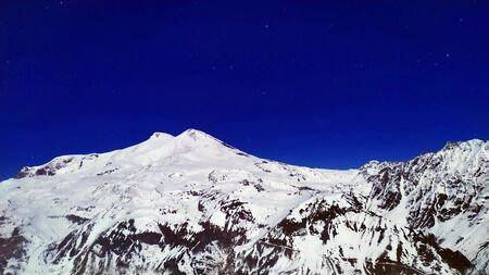 Landscape of beautiful slopes of the Caucasus Mountains over night sky with stars, Elbrus